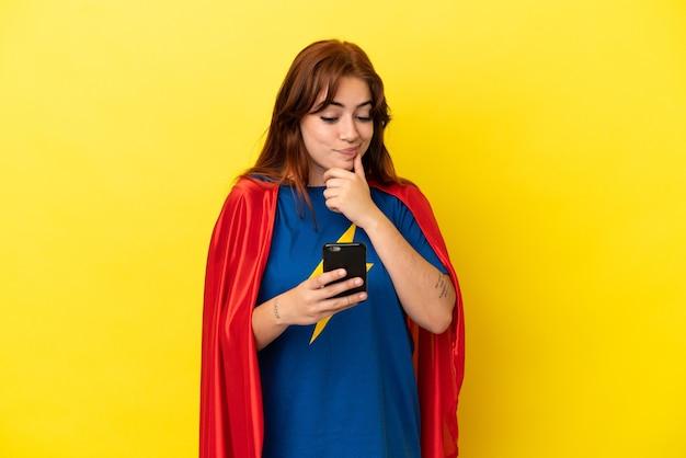 Рыжая женщина супергероя изолирована на желтом фоне, думая и отправляя сообщение
