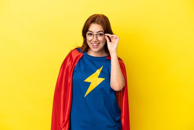 Рыжая женщина супергероя изолирована на желтом фоне в очках и удивлена