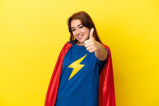 슈퍼 히어로 빨간 머리 여자는 좋은 일이 일어났기 때문에 엄지손가락을 들고 노란색 배경에 고립되었습니다