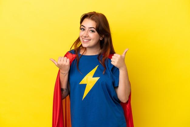 노란색 배경에 고립된 슈퍼 히어로 빨간 머리 여성, 엄지손가락 제스처와 미소