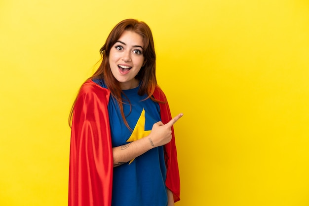 Super hero redhead woman isolated on yellow background surprised and pointing side