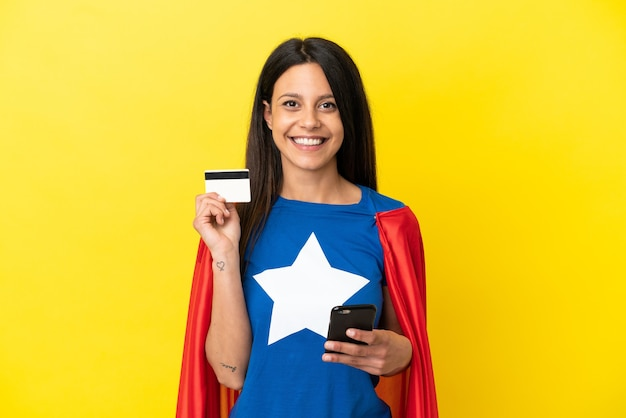 Женщина супергероя изолирована на желтом фоне, покупая с мобильного с помощью кредитной карты