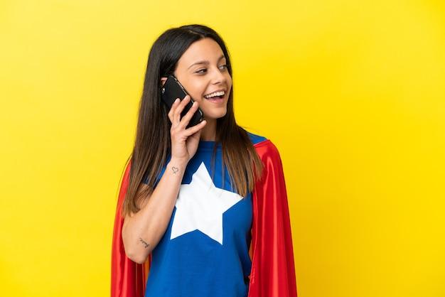 Женщина супергероя изолирована на желтом фоне, разговаривая с кем-то по мобильному телефону