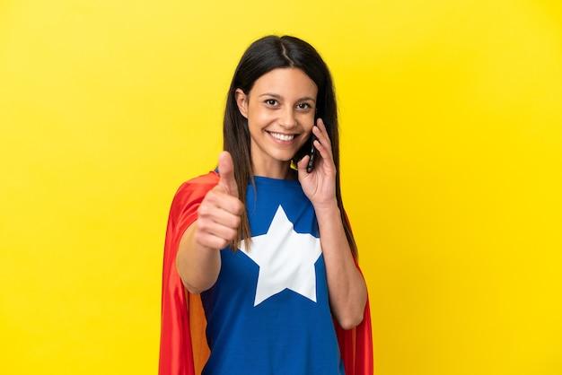 노란색 배경에 격리된 슈퍼 히어로 여성은 엄지손가락을 치켜들면서 모바일과 대화를 유지합니다.
