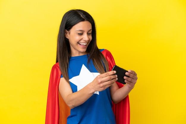 Женщина супергероя изолирована на желтом фоне, играя с мобильным телефоном