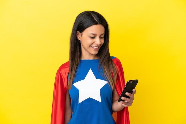 Женщина супергероя изолирована на желтом фоне, отправляя сообщение или электронное письмо с мобильного телефона