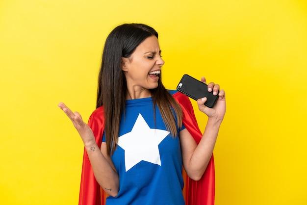 Женщина супергероя изолирована на желтом фоне с помощью мобильного телефона и поет