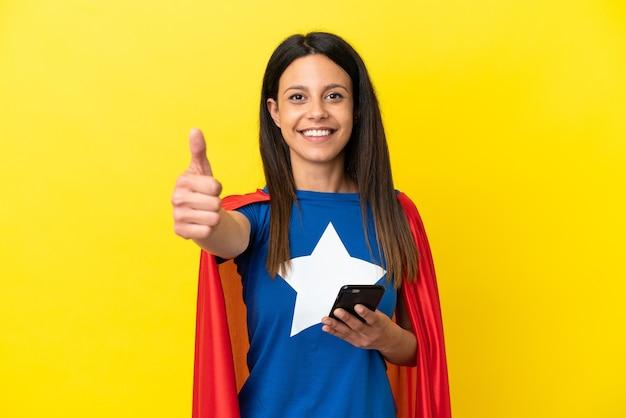 엄지손가락을 치켜드는 동안 휴대전화를 사용하여 노란색 배경에 고립된 슈퍼 히어로 여성
