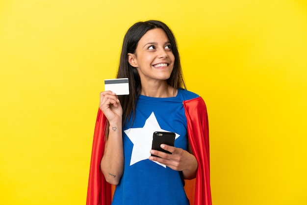 Super hero woman isolated on yellow background buying with the mobile with a credit card while thinking