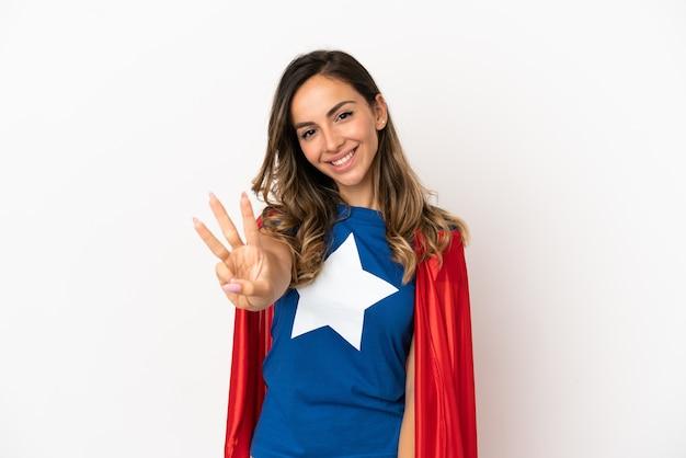 孤立した白い背景の上のスーパーヒーローの女性は幸せで、指で3つを数えます