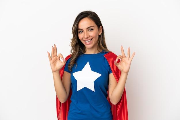 Женщина супергероя на изолированном белом фоне, показывая пальцами знак ок