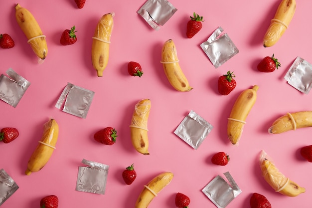 Preservativi super sicuri al gusto di banana e fragola con odore gradevole su sfondo roseo in studio. contraccettivi in lattice di gomma naturale, materiale di alta qualità. sensazione naturale e sicurezza.
