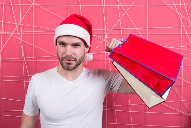 Супер санта покупатель с бумажными мешками на розовом фоне. человек в шляпе xmas держит сумки в сильной руке. зимняя распродажа, концепция покупок. рождественские и новогодние подарки. каникулы тренировки и тренировки.