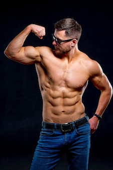 Super sexy man with tan abs and chest. athletic man with no shirt, naked torso. gray background pumping muscles. studio portrait