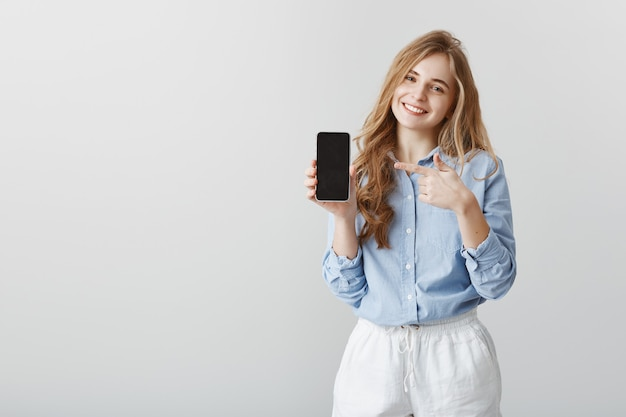 Super useful device. pleased good-looking female student with blond hair in blue-collar shirt, showing black smarpthone and pointing at gadget with index finger, offering to buy item