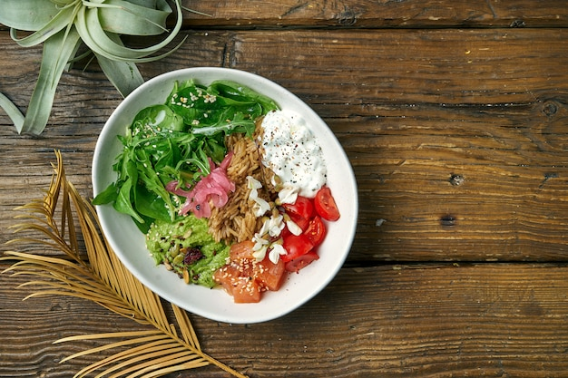 Superfood - a bowl with rice, salmon, guacamole, poached egg and cherry tomatoes seasoned with greek yogurt on a wooden. balanced food