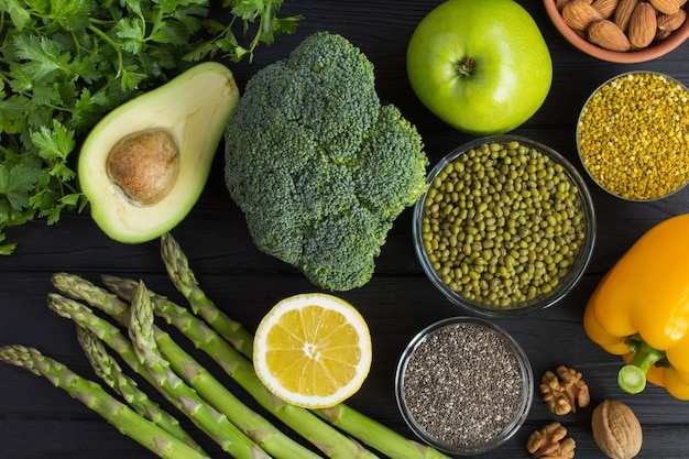 スーパーフードやベジタリアン料理のコンセプトです。黒い木製の背景に野菜、果物、豆類、ナッツ、蜂の花粉。トップビュー。