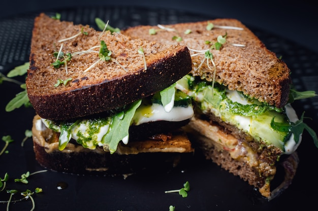 Superfood sandwich with whole grain bread, cucumber, egg whites, radishes and pea shoots on plate. isolated on black background, close up,