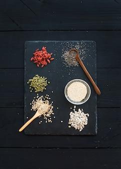 Superfoods on black chalkboard: goji berries, chia, mung beans, buckwheat, quinoa, sunflower seeds. top view