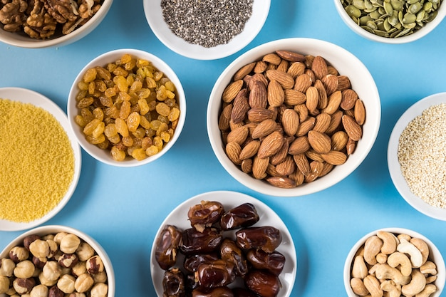 Superfoods in bowls on blue background.