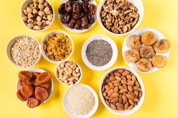 Superfoods in bowls on yellow background.
