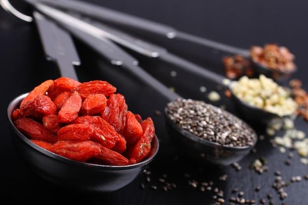 Superfoods. goji berries, chia seeds, hemp seeds and broken flax seeds in metal measuring spoons