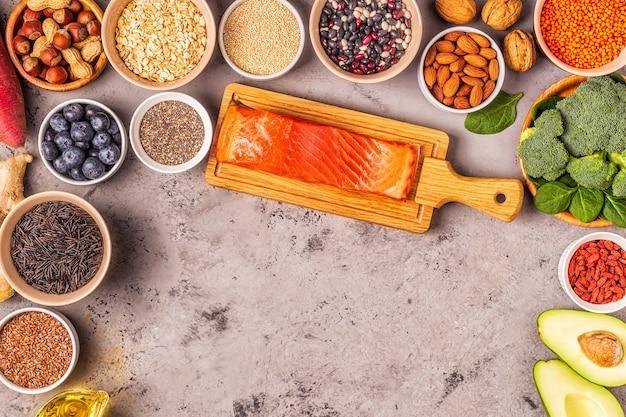 灰色のコンクリートの背景にスーパーフード。健康食品のきれいな食事の概念。上面図。