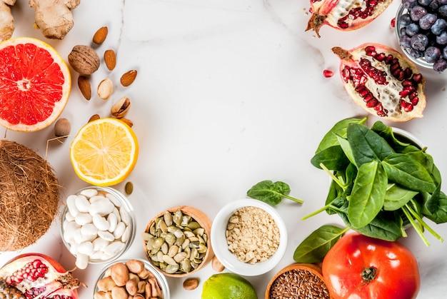 Комплект органической еды здорового питания, superfoods - фасоли, бобов, гаек, семян, зеленых цветов, фруктов и овощей. белый космос экземпляра предпосылки. вид сверху