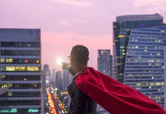 Superhero businessman looking at city skyline at sunset. the concept of success,