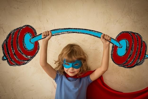 Ребенок супергероя на фоне стены гранж. концепция успеха и победителя