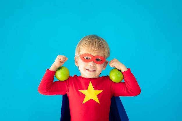 Superhero child holding apple