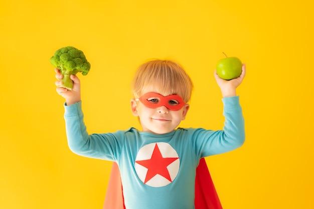 Ребенок супергероя, держащий брокколи и яблоко