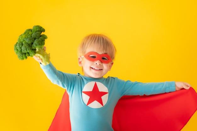 Superhero child holding broccoli