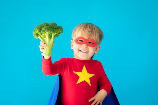 ブロッコリーを保持しているスーパーヒーローの子供。