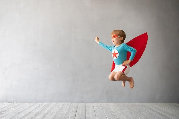 灰色のコンクリートの壁にジャンプするスーパーヒーローの子供。