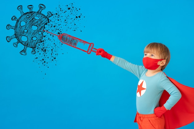 실내 보호 마스크를 착용하는 슈퍼 히어로 아이. 파란색 종이 배경 슈퍼 영웅 아이의 초상화.