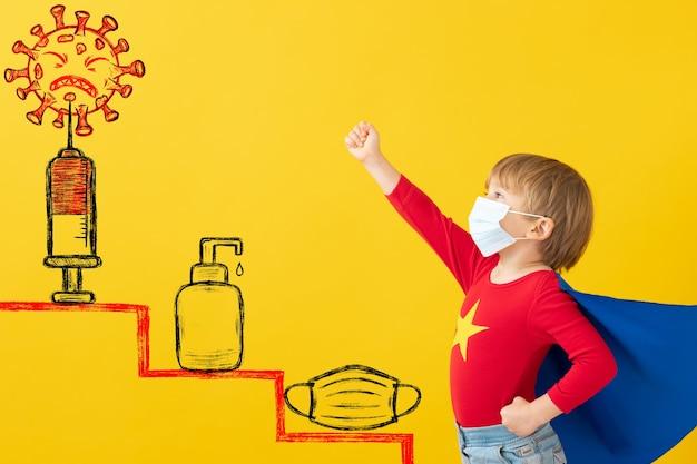 실내 보호 마스크를 착용하는 슈퍼 히어로 아이. 노란 종이 배경 슈퍼 영웅 아이의 초상화.