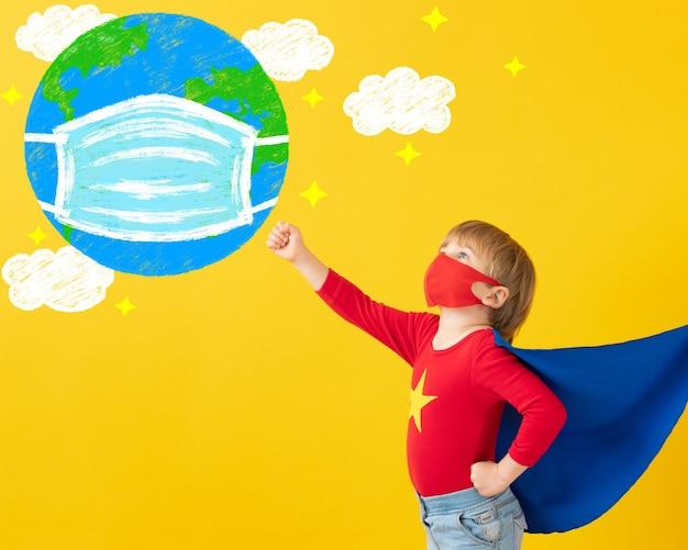 屋内で保護マスクを着用しているスーパーヒーローの子供。黄色い紙の背景にスーパーヒーローの子供の肖像画。
