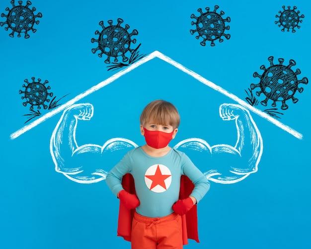 屋内で保護マスクを着用しているスーパーヒーローの子供