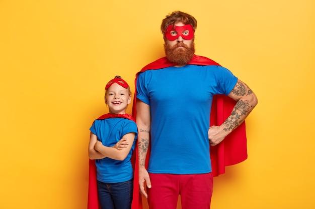 Famiglia di supereroi. il potente papà tiene una mano sulla vita, il bambino con le braccia incrociate si alza