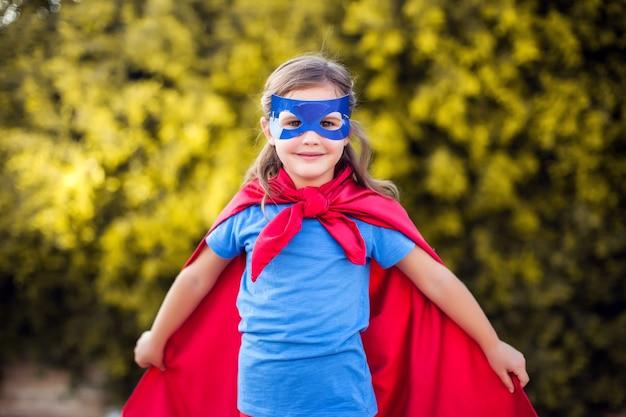 Девушка супергероя против зеленого на открытом воздухе