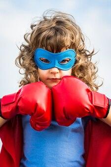 푸른 하늘 배경에 권투 장갑을 끼고 슈퍼 히어로 아이. 걸 파워와 페미니즘 개념