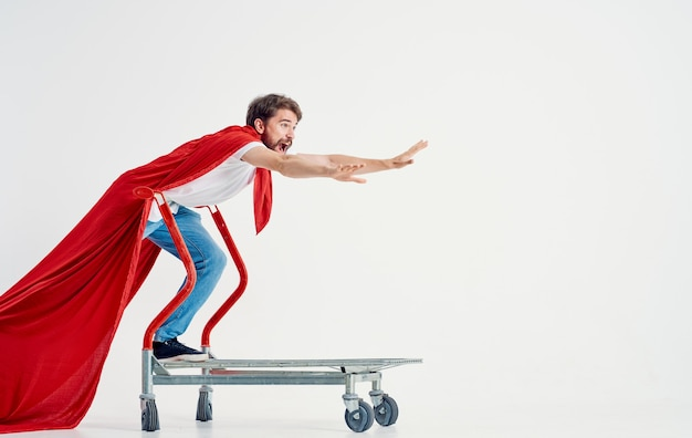 A superhero in a red cloak stands on a cargo cart in a bright room