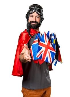 取引をしている多くの旗を持つスーパーヒーロー