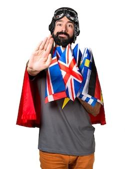 Супергерой с большим количеством флагов, делающих знак остановки