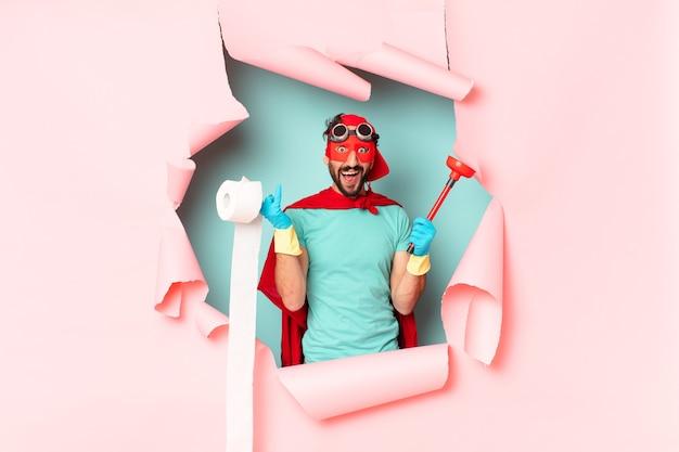 Superhero with bathroom items behind broken paper wall
