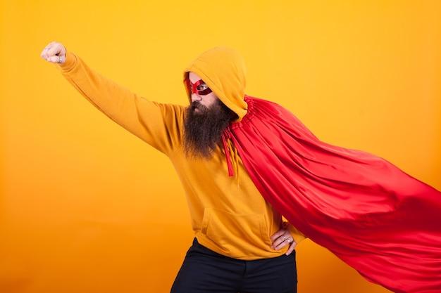 빨간 망토와 마스크를 쓴 슈퍼히어로가 스튜디오에서 노란색 배경 위로 날아가고 있습니다., 용감한 남자. 멋진.