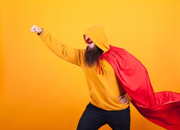 Superhero with red cape and mask flying away in studio over yellow background., brave man. handsome.