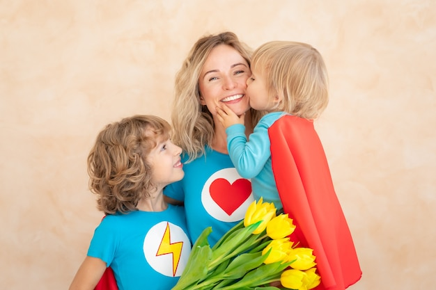 Superhero woman and children at home