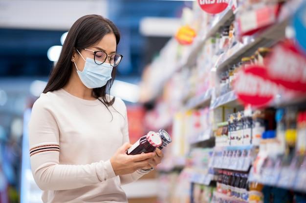 Покупки маски азиатской женщины нося в supermaket во время вируса короны
